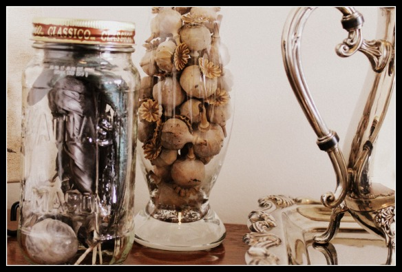 Feathers in an old jar, poppy seedpods in a vase and a silver tea service
